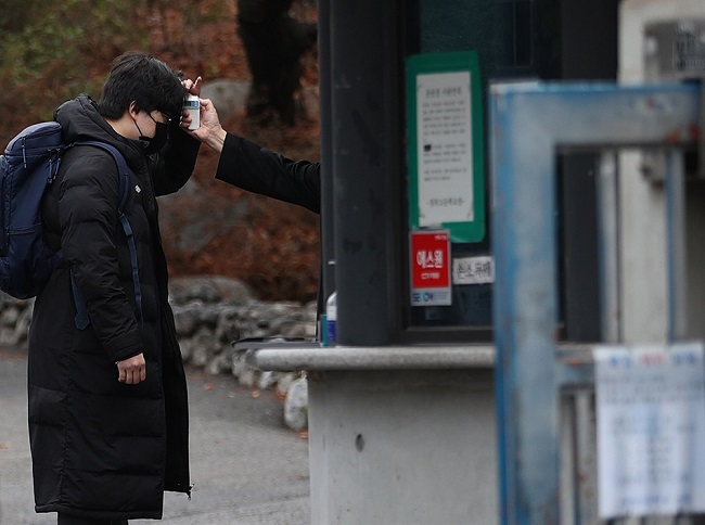 A student has his temperature checked before entering school at Kyungbock High School in Seoul on March 2, 2021. (Yonhap)