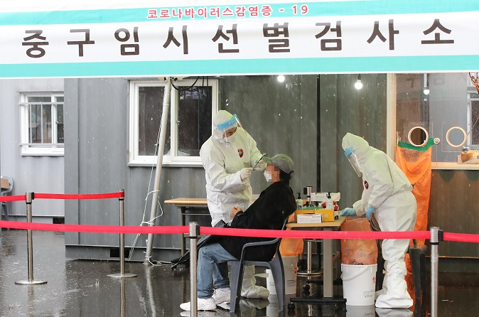 Health workers conduct a new coronavirus test on a citizen at a temporary testing site in front of Seoul Station in central Seoul on March 1, 2021. (Yonhap)