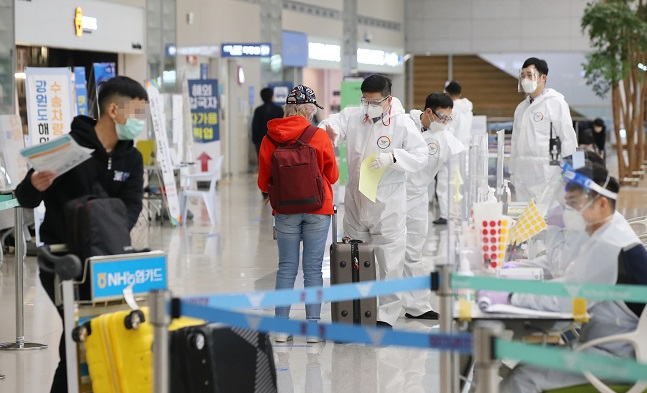 Health workers clad in protective suits guide foreign arrivals at Incheon International Airport in Incheon on March 4, 2021. (Yonhap)