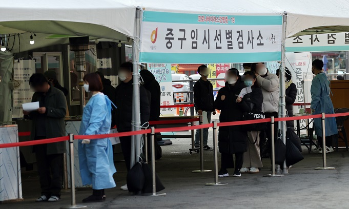People wait in line to receive new coronavirus tests at a temporary testing site set up in front of Seoul Station in central Seoul on March 7, 2021. South Korea reported 416 more COVID-19 cases, raising the total caseload to 92,471. (Yonhap)