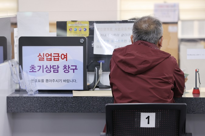 This March 24, 2021, photo shows a man talking to a counselor to receive state unemployment benefits at a job center in western Seoul. (Yonhap)