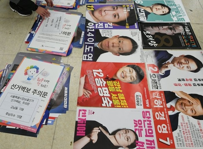 Officials classify posters showing contenders for the April 7 Seoul mayoral by-election at an election management committee in Seoul on March 24, 2021. (Yonhap)