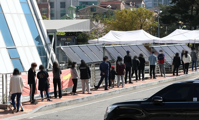 Citizens wait in a line to receive COVID-19 tests at a makeshift clinic in Daejeon, 164 kilometers south of Seoul, on April 7, 2021. (Yonhap)