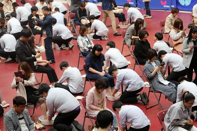 Students at Dongsan High School in Daejeon, 164 km south of Seoul, wash the feet of their parents during an event to mark Parents' Day on May 8, 2019. (Yonhap)