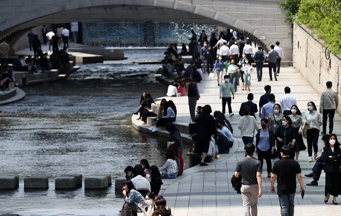 Citizens rest along the Cheonggye Stream in downtown Seoul on April 21, 2021, as the daily high recorded 26 C. (Yonhap)