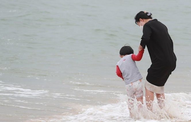 A mother and her boy play in the water at Haeundae Beach in the southeastern port city of Busan on April 22, 2021, amid early summer weather and an intraday high temperature of 23 C. (Yonhap)
