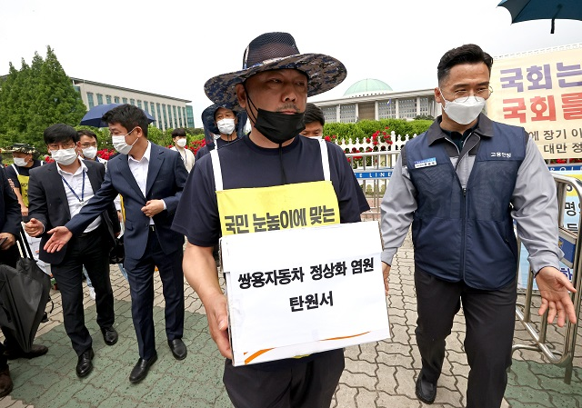 Chung Il-kwon (C), union leader of financially troubled SsangYong Motor Co. under court receivership, enters the National Assembly in Seoul on May 20, 2021, to submit petitions calling for lawmakers to help address the ailing company's management crisis. (Yonhap)