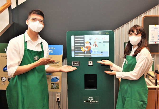 In this photo provided by Starbucks Korea, models pose for a photo at its outlet in Jeju Island to advertise reusable cup deposit system.