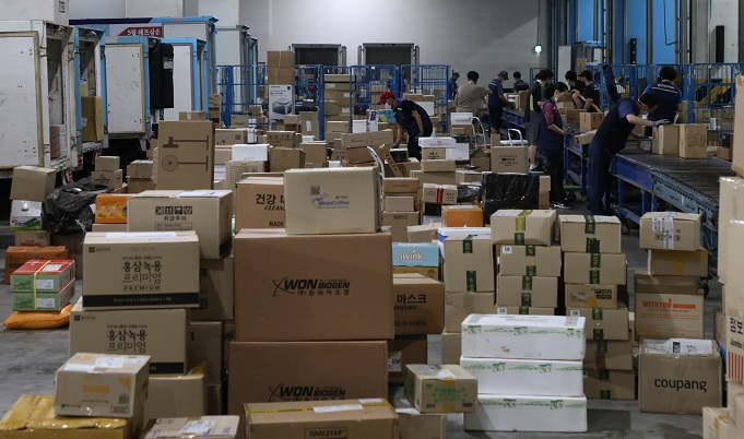 Workers sort parcels at a distribution center in eastern Seoul on June 9, 2021. (Yonhap)
