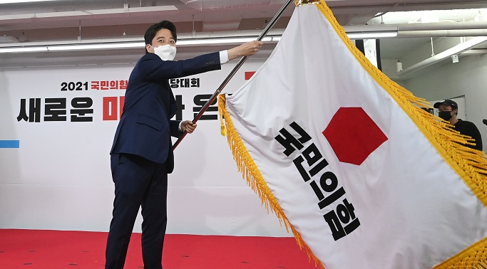 Lee Jun-seok waves the flag of the People Power Party after winning the party's chairmanship in a party convention on June 11, 2021. (Yonhap)