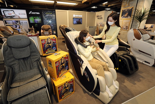 This photo provided by E-Mart Inc. shows models promoting massage chair.