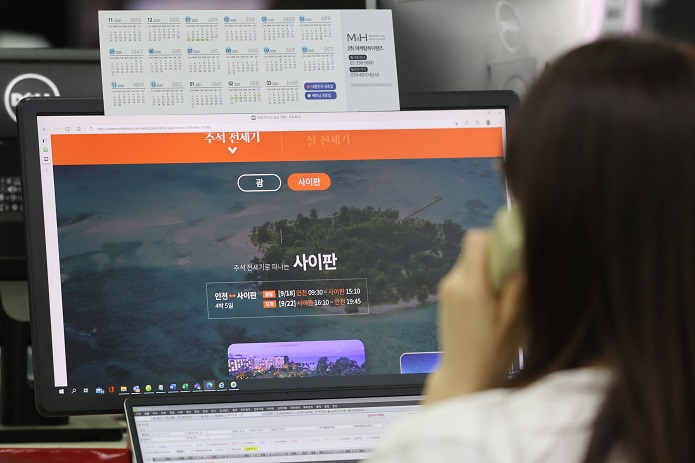 This file photo, taken on June 21, 2021, shows an official at travel agency No.2 Mode Tour talking on the phone in front of a computer screen showing an overseas tour schedule for the holidays of Chuseok's fall harvest.  (Yonhap)