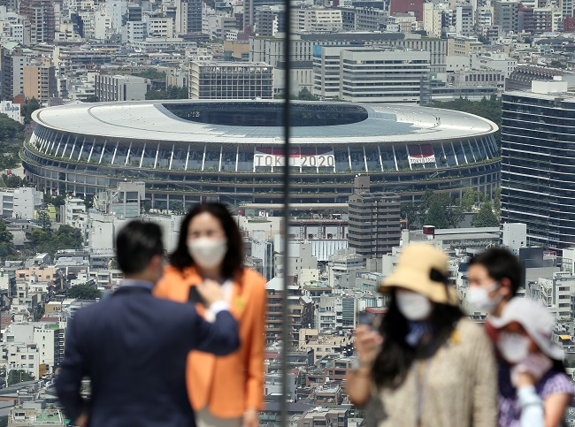 Visitors at an observation tower in Tokyo take pictures with the National Stadium, site of the opening ceremony for the Tokyo Olympics, in the background on July 21, 2021. (Yonhap)
