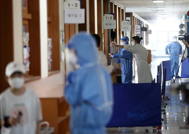 Quarantine officials work at temporary testing stations set up at an elementary school in Daejeon on July 22, 2021. (Yonhap)
