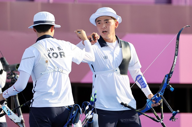 South Korean archers An San (L) and Kim Je-deok bump fists during the mixed team event final at the Tokyo Olympics at Yumenoshima Park Archery Field in Tokyo on July 24, 2021. (Yonhap)