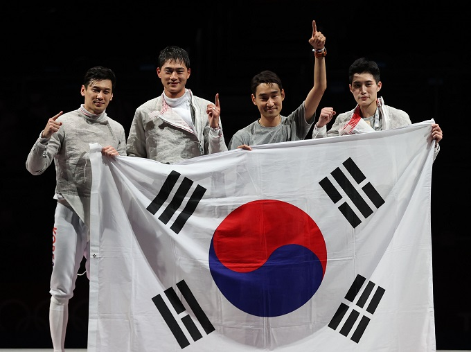 South Korean fencers Gu Bon-gil, Oh Sang-uk, Kim Jung-hwan and Kim Jun-ho (L to R) celebrate their victory over Italy in the final of the men's team sabre fencing event at the Tokyo Olympics at Makuhari Messe Hall B in Chiba, Japan, on July 28, 2021. (Yonhap)