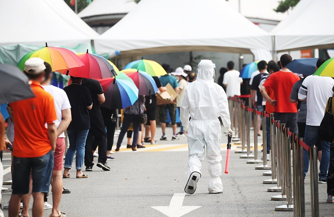 People wait in line to get tested for COVID-19 amid the country's scorching summer heat outside a screening center in Ansan, 42 kilometers south of Seoul, on July 29, 2021. (Yonhap)