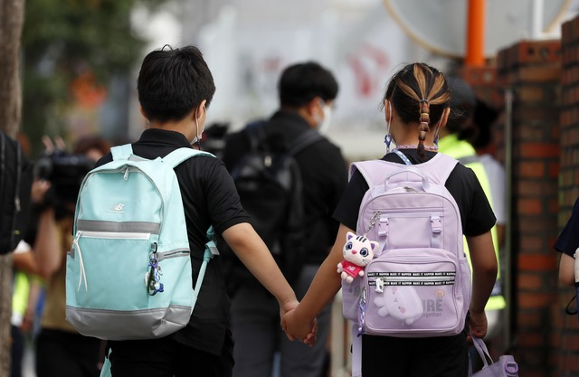 Siblings go to school after the summer vacation in Seoul on Aug. 17, 2021. (Yonhap)