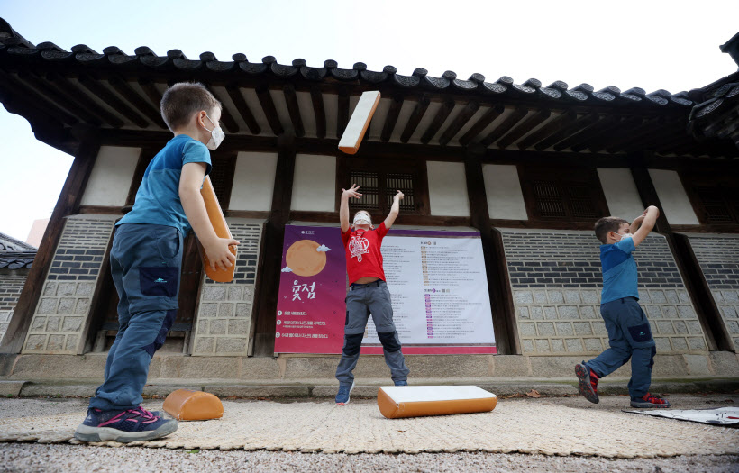 """Foreign children play """"yutnori,"""" a Korean traditional board game, during Chuseok, the Korean equivalent of Thanksgiving, at Unhyeon Palace in central Seoul on Sept. 21, 2021. (Yonhap)"""