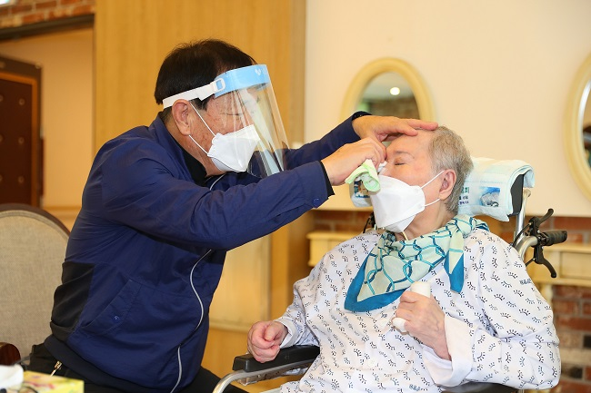A man wipes away his wife's tears at a nursing home in Gwangju, Gyeonggi Province, on Sept. 20, 2021. The couple met in person for the first time in two months as the government has enforced special quarantine steps for the Chuseok holiday amid the new coronavirus, in this photo provided by the health ministry.