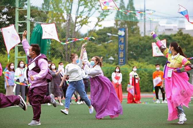 This Sept. 25, 2020, file photo shows foreign students wearing the traditional Korean costume hanbok and flying kites at a university in Daegu ahead of the Chuseok holiday. (Yonhap)