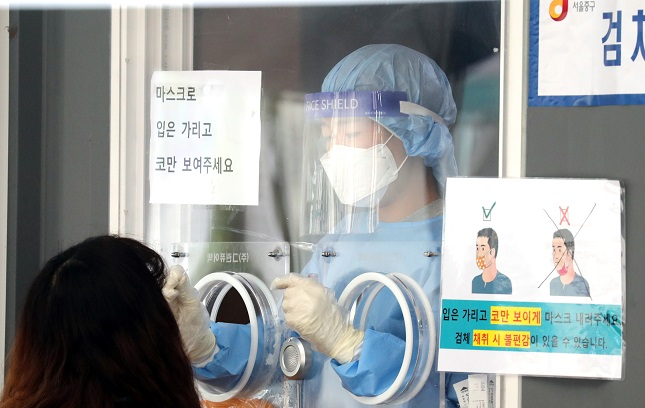 A health worker clad in a protective suit collects a sample from a citizen at a makeshift COVID-19 testing clinic in Seoul on Sept. 12, 2021. (Yonhap)