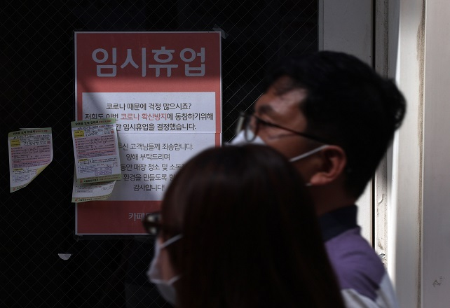 People wearing masks pass by a cafe showing a closure notice in Seoul on Sept. 15, 2021. (Yonhap)