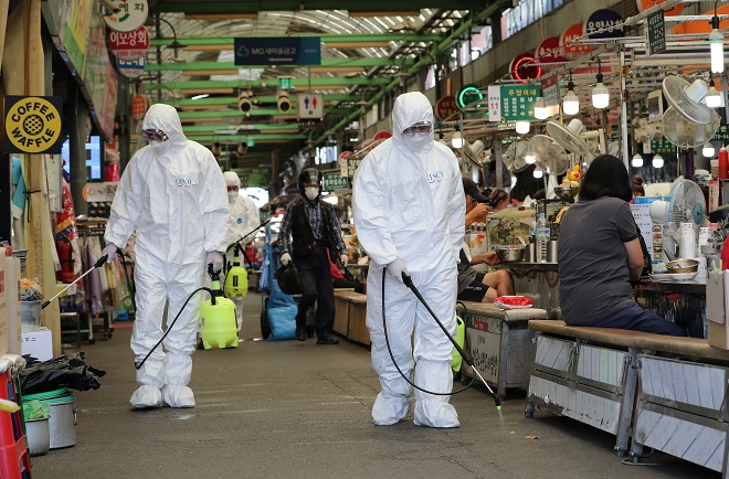 Health workers in protective gear disinfect a traditional market in Seoul on Sept. 16, 2021. (Yonhap)