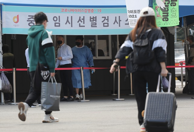 Travelers walk past a screening clinic for coronavirus tests in front of Seoul Station on Sept. 17, 2021, the eve of a five-day break for Chuseok, the Korean harvest holiday that falls on Sept. 21 this year. South Korea's daily coronavirus cases exceeded 2,000 the same day amid concerns the holiday, when tens of millions of people are expected to travel across the country, may cause further upticks in virus cases. (Yonhap)